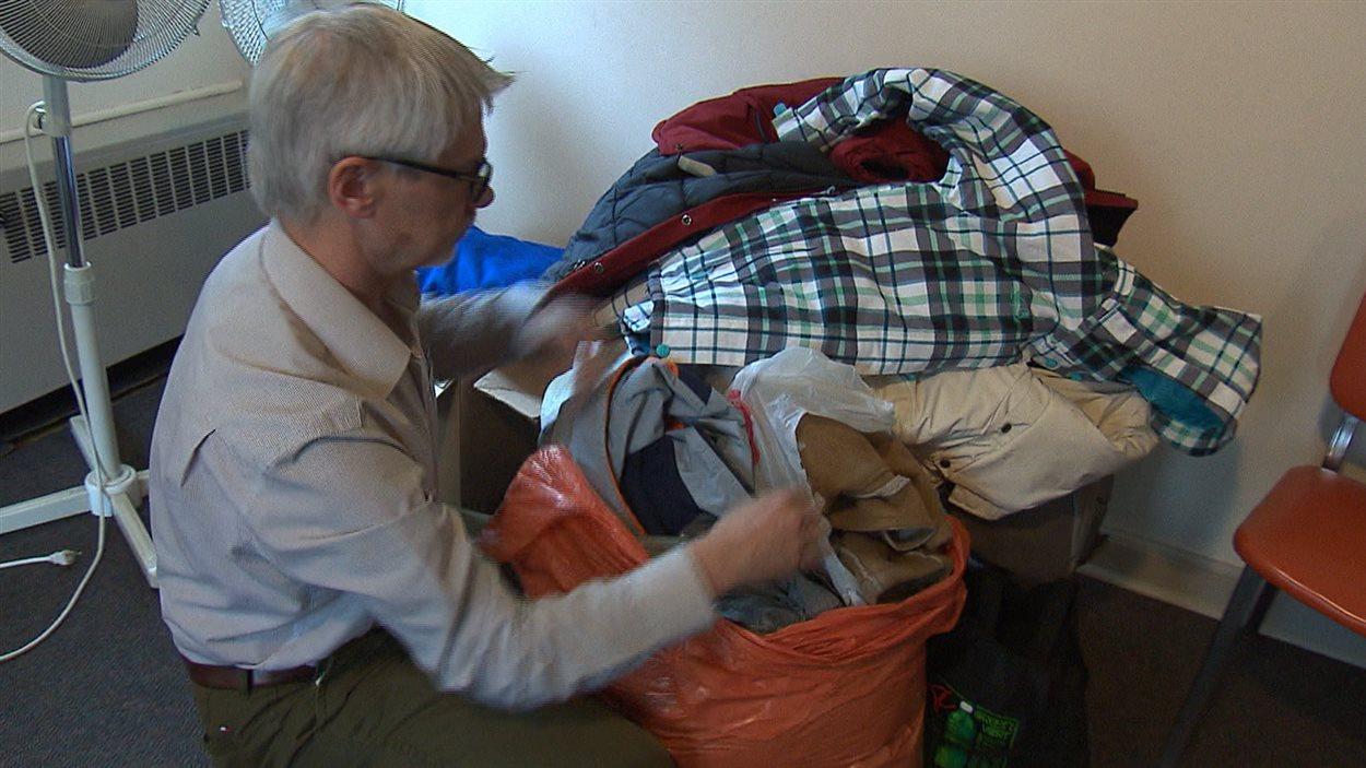 Paul Clarke, directeur d'action réfugiés Montréal, montre les manteaux apportés par des donateurs à son organisme.