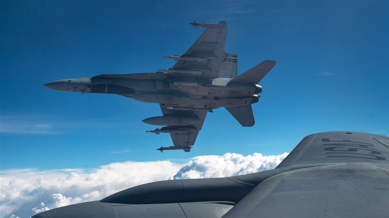 A Royal Canadian Air Force CF-18 Hornet breaks away after refueling with a KC-135 Stratotanker assigned to the 340th Expeditionary Air Refueling Squadron, Thursday,  Oct. 30, 2014 over Iraq.