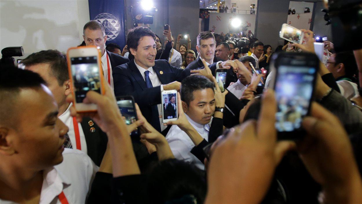 Le premier ministre Justin Trudeau entouré par des admirateurs au moment où il quitte le centre international de presse à Manille.