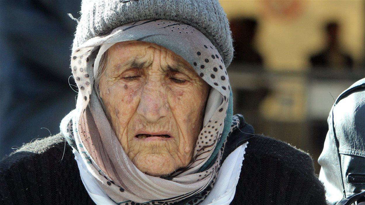 Une réfugiée syrienne âgée attend d'être enregistrée dans un camp serbe.