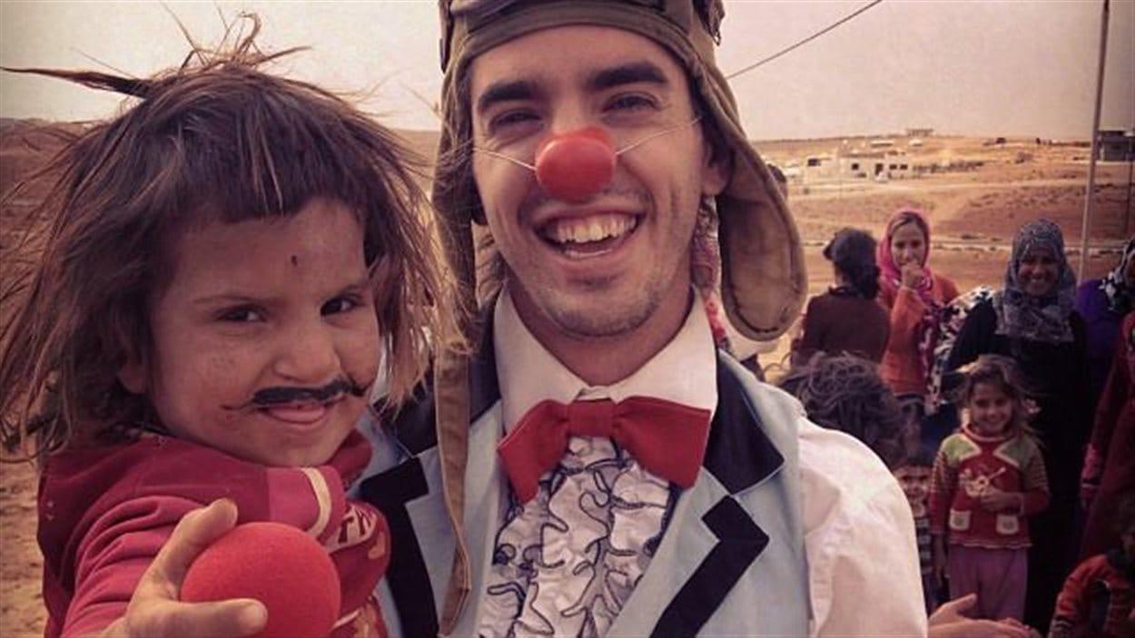Le clown Guillaume Vermette avec un enfant syrien.