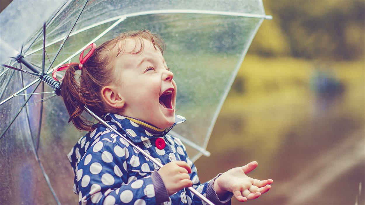 Un enfant rit sous la pluie.