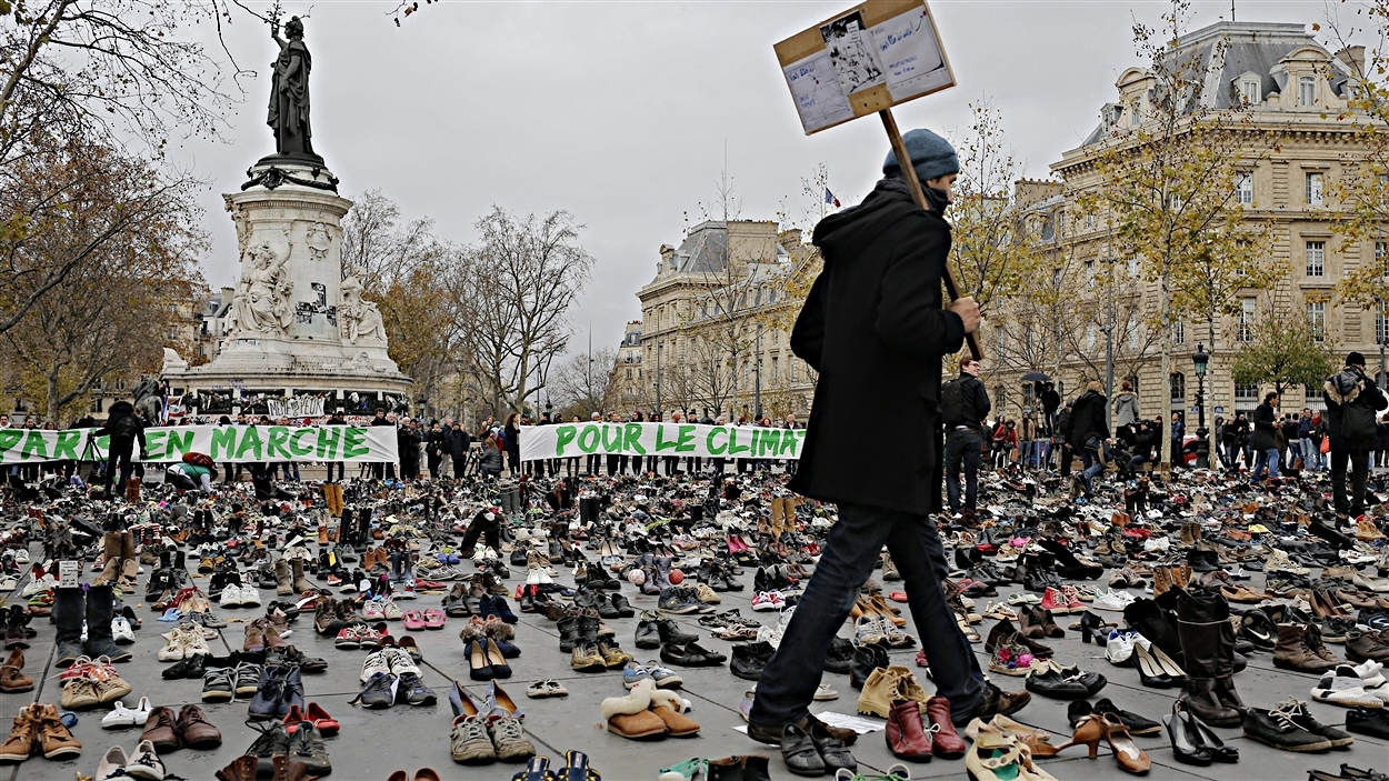 Un homme marche parmi des centaines de paires de souliers sur la place de la République, à Paris, dans le cadre de la marche soulignant l'ouverture, lundi, de la conférence Paris climat.