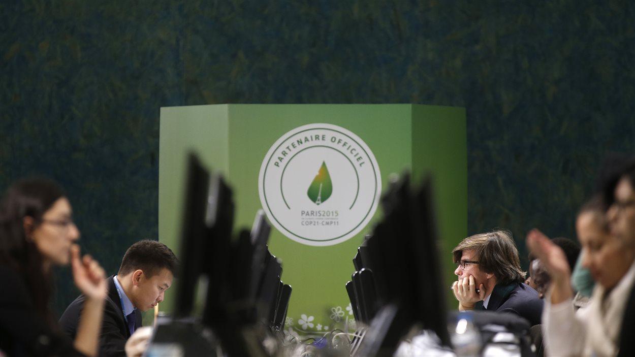 Les participants à la conférence sur le climat de Paris sont nombreux à être rivés sur des écrans.