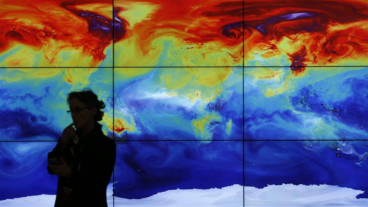 Une participante à la conférence de Paris devant une carte illustrant les bouleversements climatiques en cours