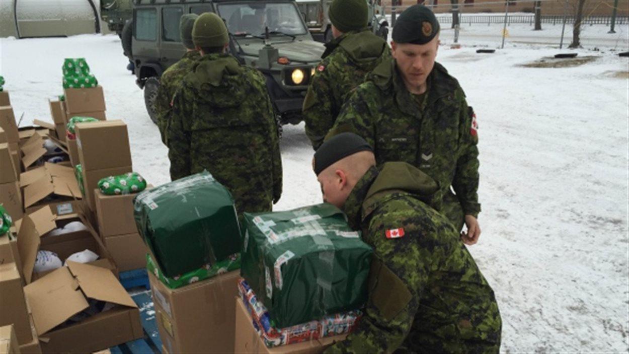 Des militaires apportent des cadeaux de Noël  dans le quartier North End de Winnipeg.