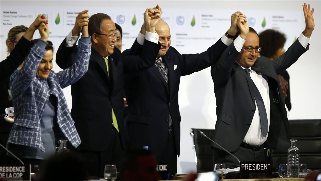 Christiana Figueres, secrétaire exécutive de la Convention-cadre des Nations unies sur les changements climatiques, Ban Ki-moon, secrétaire général des Nations unies, Laurent Fabius,  président de la conférence de Paris, et François Hollande célèbrent la conclusion d'un accord sur le climat.