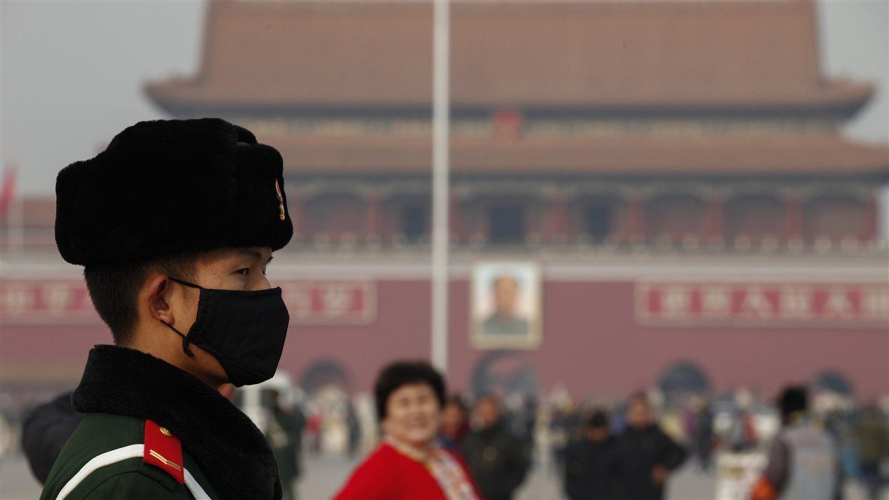 Un policier chinois posté sur la place Tiananmen porte un masque de protection contre la pollution.