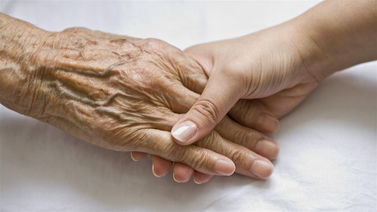 Mains d'une personne âgée et d'une personne jeune.