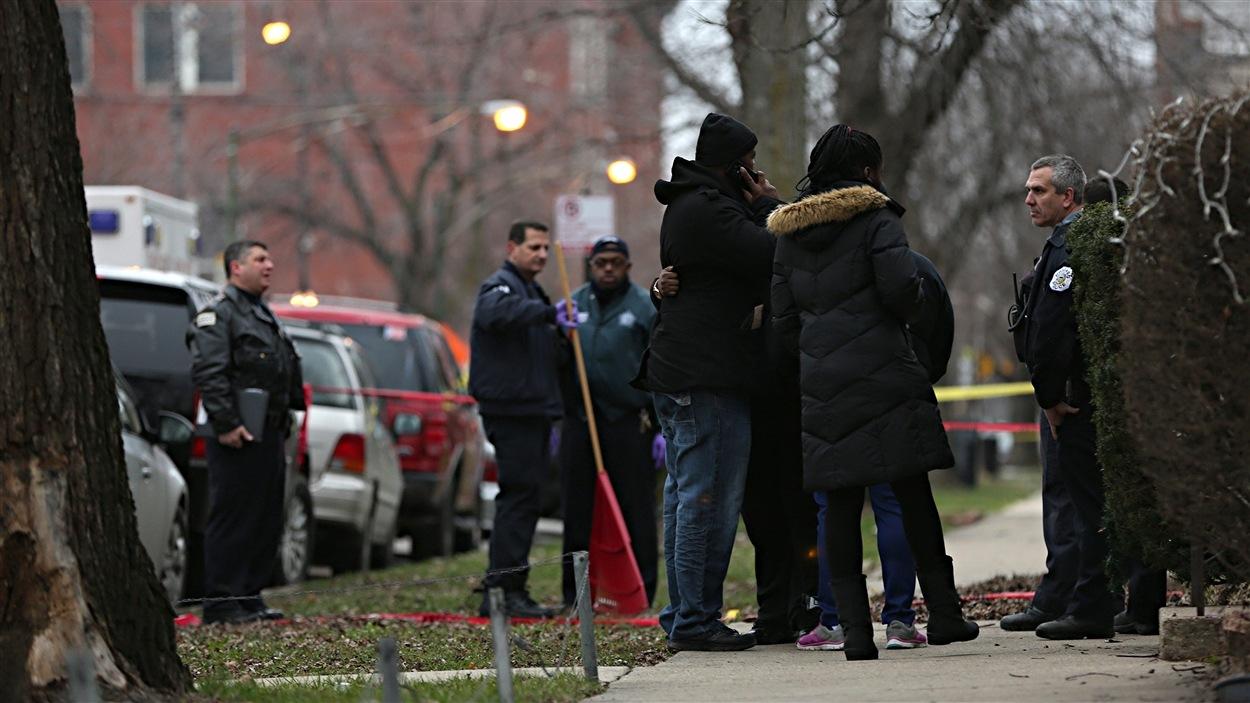 Un agent de police discute avec les proches des victimes