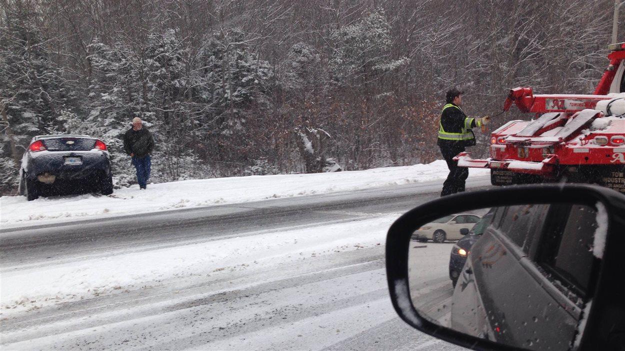 Une dépanneuse se prépare à venir en aide à un chauffeur qui a fait une sortie de route.