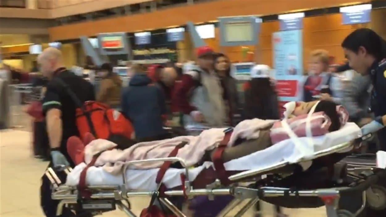 Un des passagers transportés en civière à l'aéroport de Calgary.