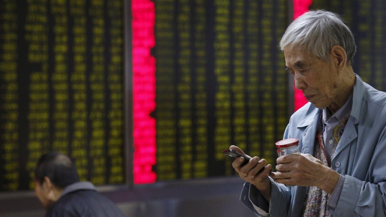 Un investisseur chinois consulte son téléphone devant une maison de courtage de Pékin.