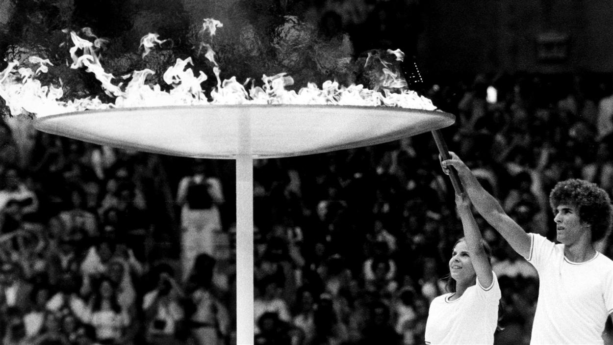 Stéphane Préfontaine et Sandra Henderson allument la vasque olympique au Stade lors de la cérémonie d'ouverture des Jeux omlympiques de Montréal, le 17 juillet 1976.