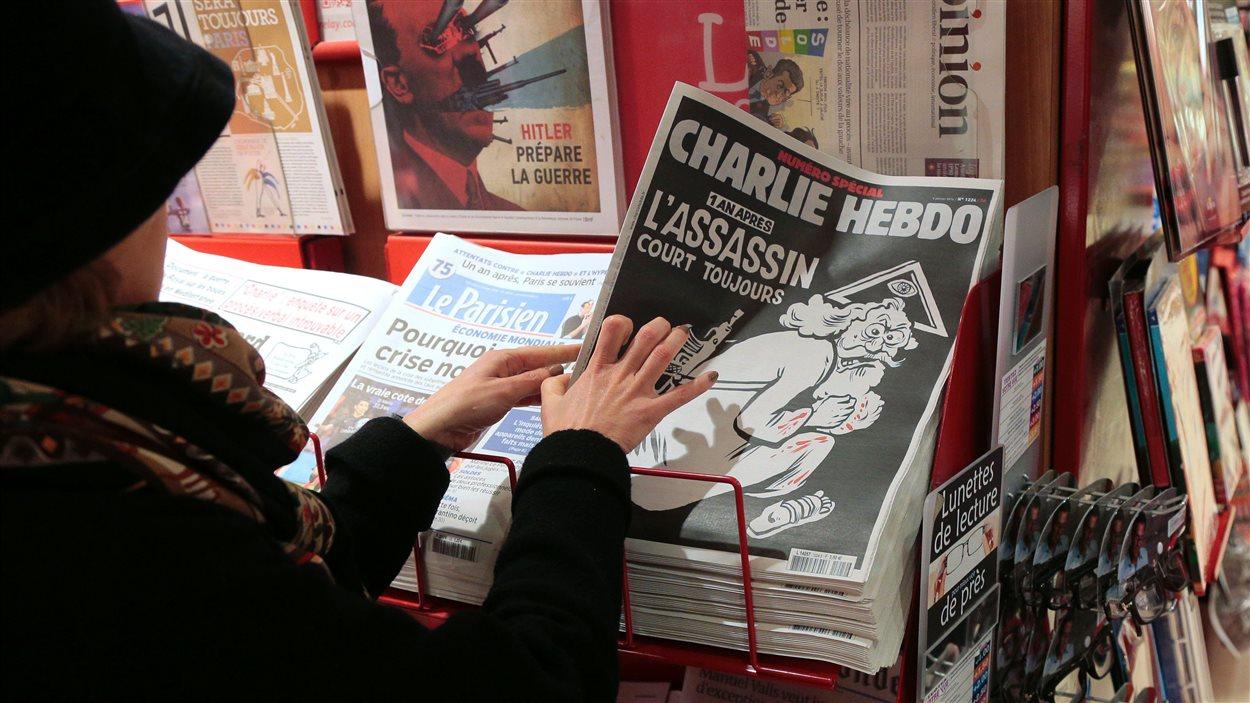Une femme prend une édition commémorative du journal satirique Charlie Hebdo à un kiosque à journaux, à Paris, le 6 janvier 2015.