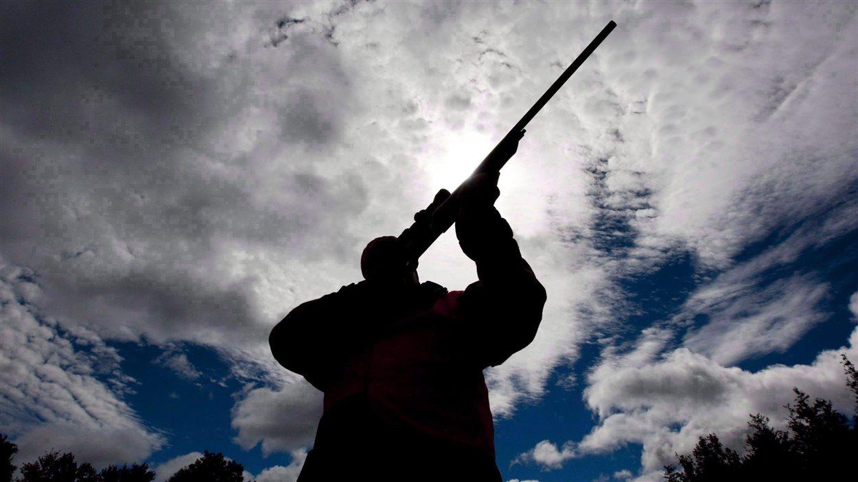 Un homme vérifie son fusil de chasse dans un camp de chasse ontarien.