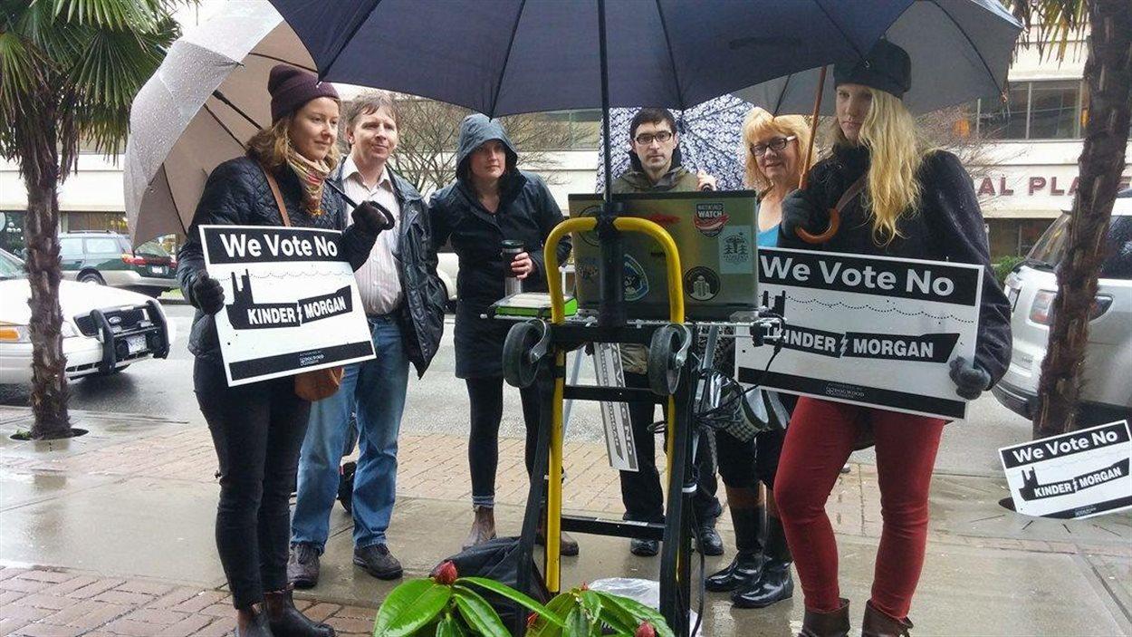 Des militants anti-pipeline rassemblés dans la rue pour regarder les audiences de l'ONÉ inaccessibles au public depuis un ordinateur.