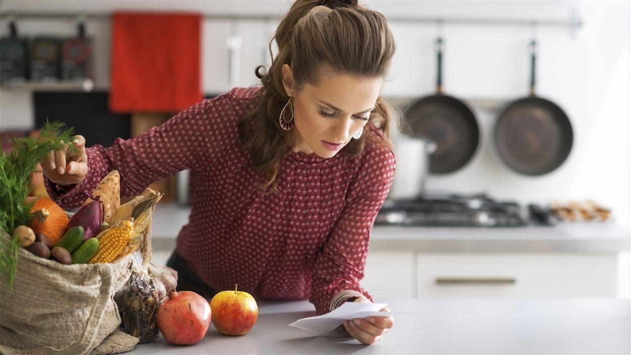 Un femme consulte sa facture d'épicerie