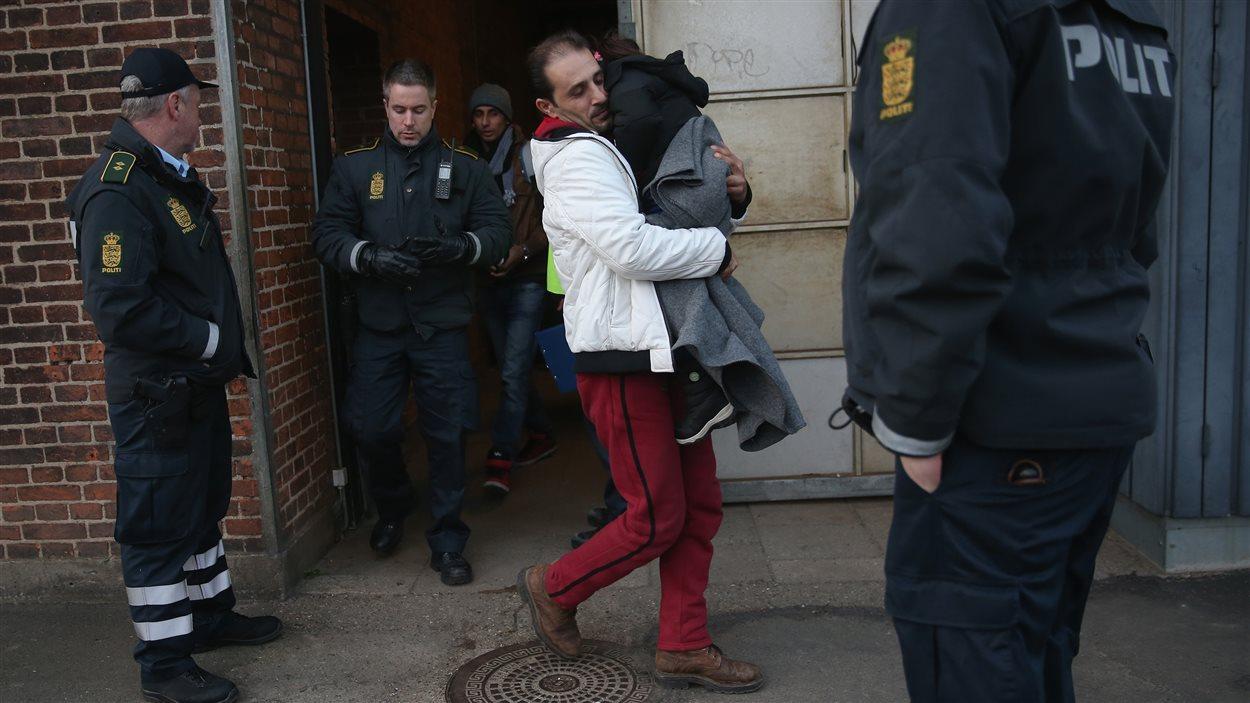 La police danoise escorte un migrant syrien et son enfant, après l'avoir intercepté dans un train, le 6 janvier. Le Danemark venait de rétablir des mesures de contrôle pour les migrants en provenance d'Allemagne.