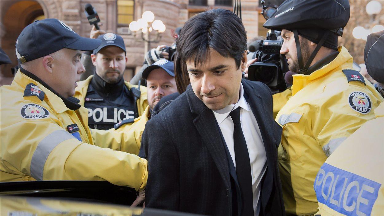 Jian Ghomeshi quitte le tribunal escorté par des policiers.