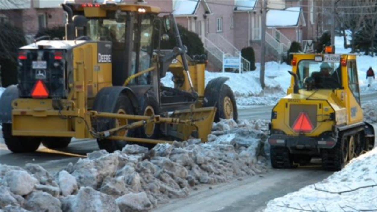 Une équipe de déneigement est constituée d'un souffleur, d'une niveleuse, d'une chenillette à trottoirs, d'un véhicule de sécurité et de camions de transport de la neige.