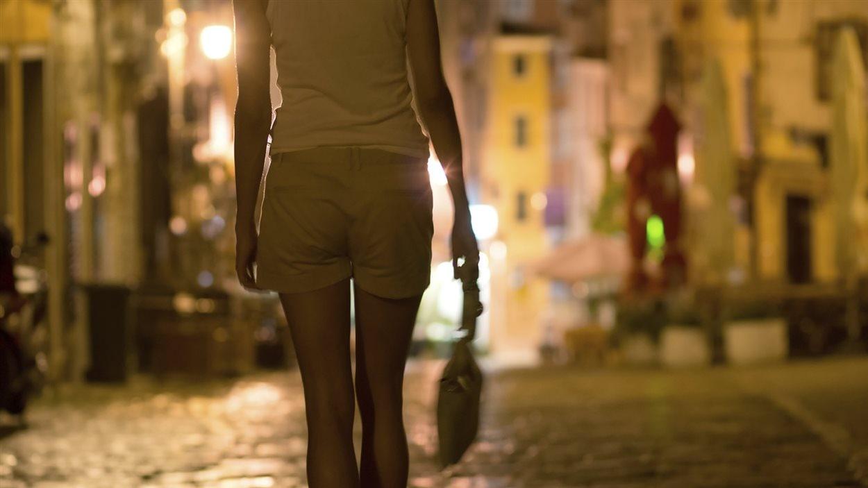 Une femme marche seule dans une rue sombre.