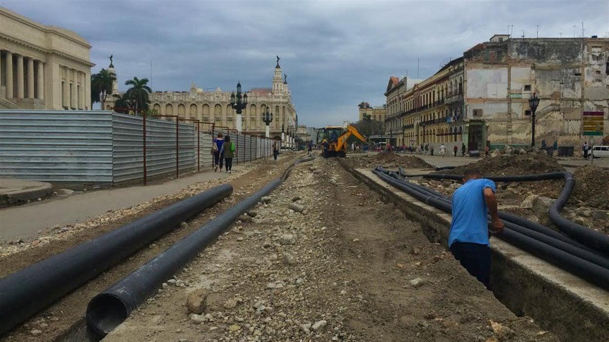 Des ouvriers installent des tuyaux devant le Capitole de La Havane.