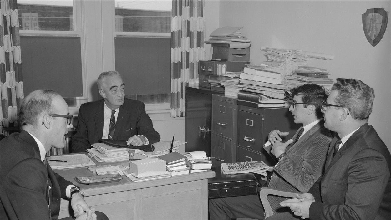 De gauche à droite : Georges Labelle, Wilfrid Sabourin, président, le journaliste du Petit Journal, et Jean-Pierre Bélanger, secrétaire, le 5 novembre 1966.