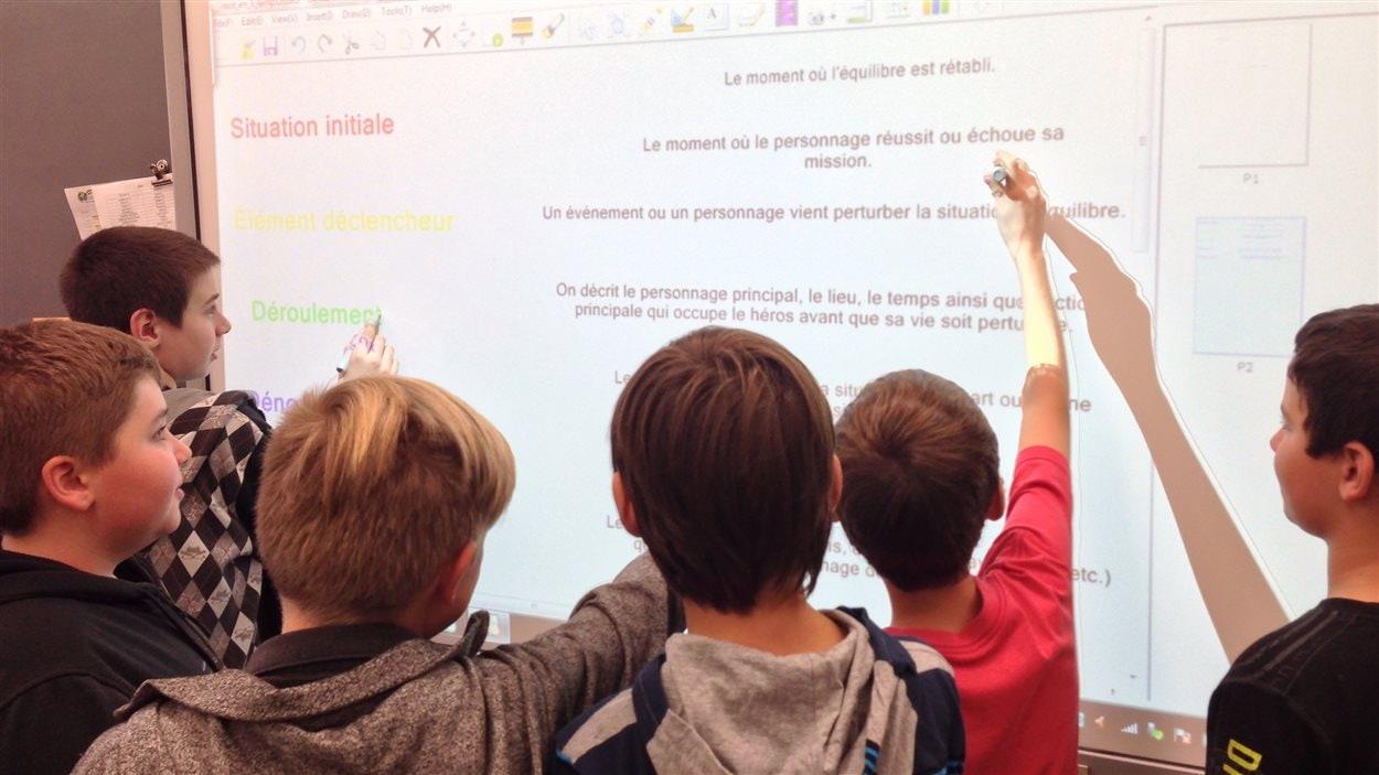 Des élèves apprennent avec un tableau numérique intéractif.