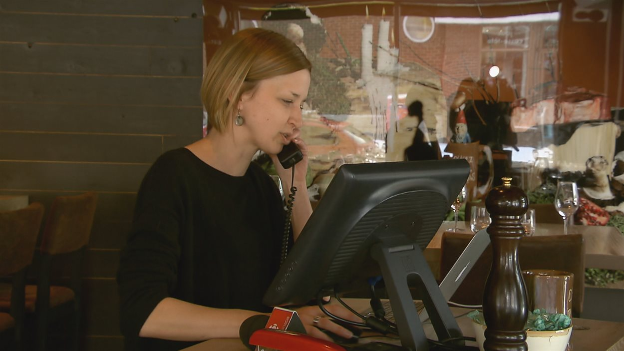 Une femme répond à un appel dans un restaurant.