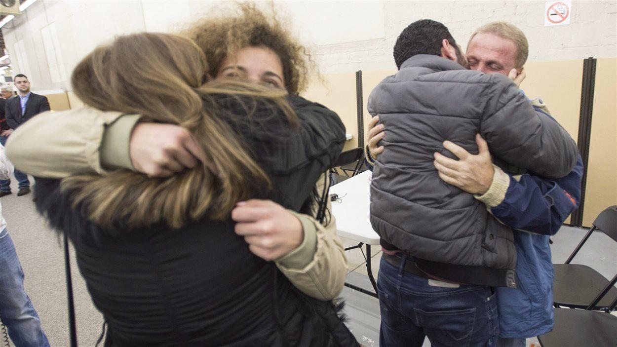 Des réfugiés partis d'Alep en Syrie sont accueillis à leur arrivée à Montréal par des membres de leur famille, en décembre 2015.