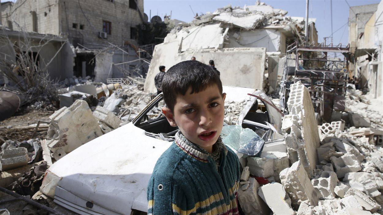 Un jeune garçon devant l'une des piles de décombres qui se trouvent à Douma, l'un des quartiers de Damas contrôlé par les rebelles.