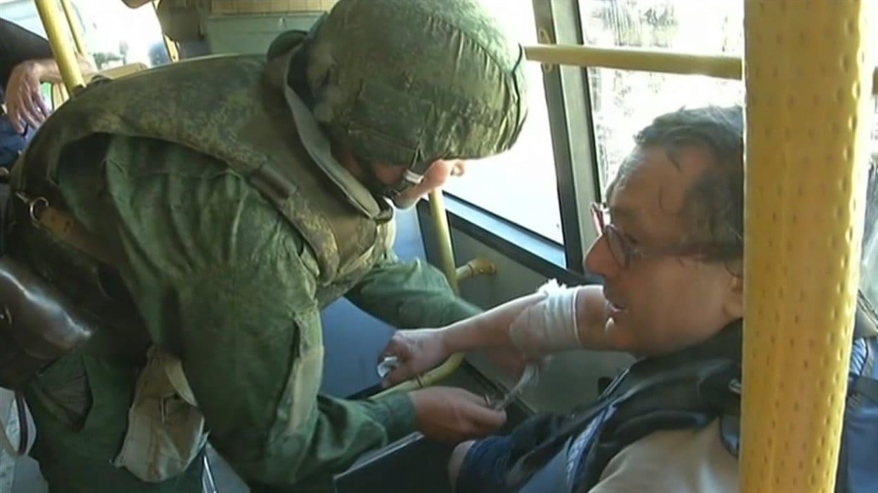 Le journaliste Raymond Saint-Pierre reçoit les premiers soins après avoir été blessé.
