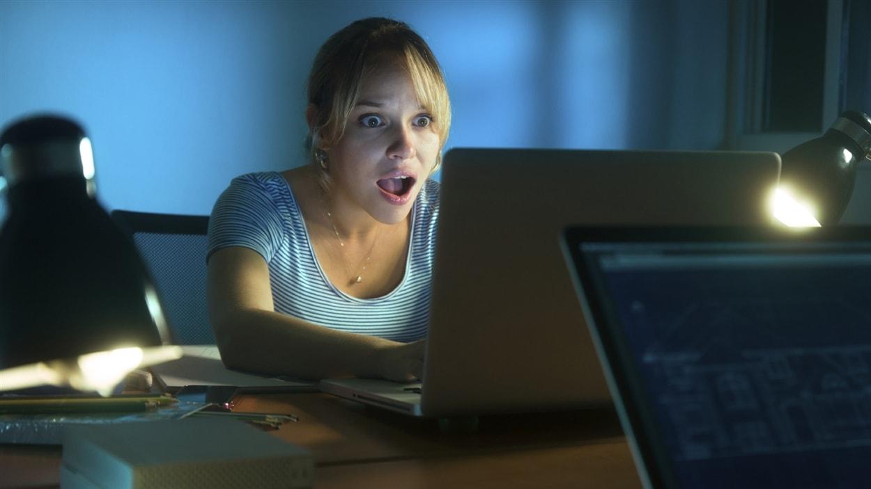 Une jeune femme vit des émotions fortes en consultant Facebook.