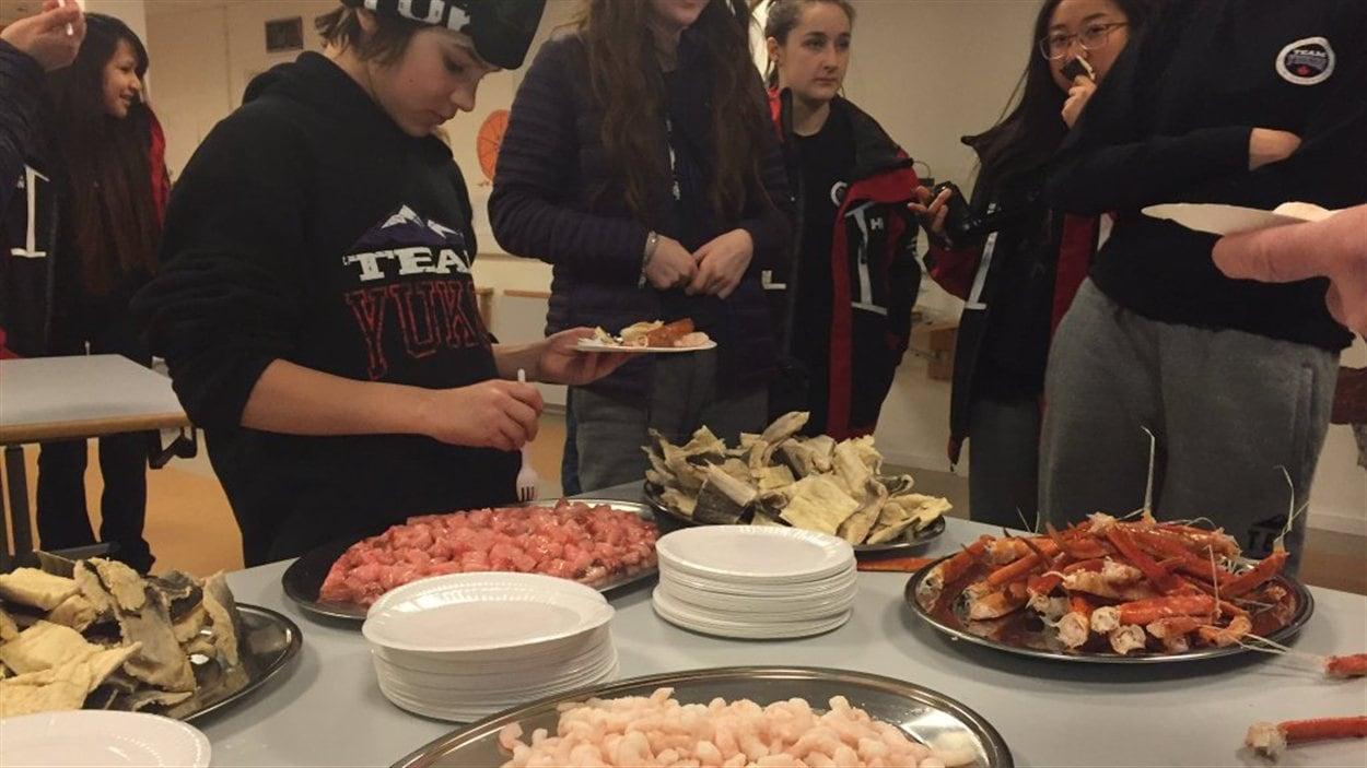 des jeunes de l'équipe du Yukon goûtent aux plats typiques offerts par les bénévoles