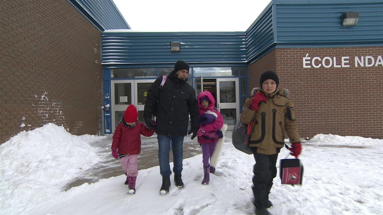 Mahmoud Alnassan et ses trois enfants, à la sortie de l'école NDA.
