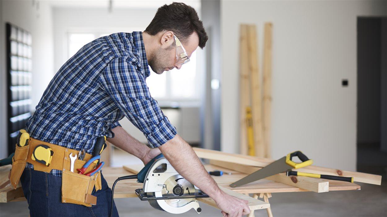 Un homme coupe une planche de bois