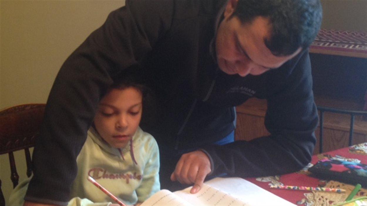 La petite de neuf ans fait ses devoirs avec son père à la maison.