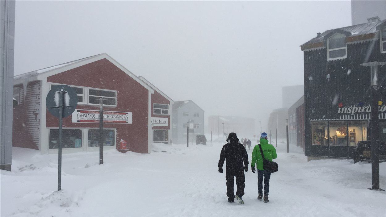 deux hommes marchent une rue piétonnière à Nuuk dans la tempête