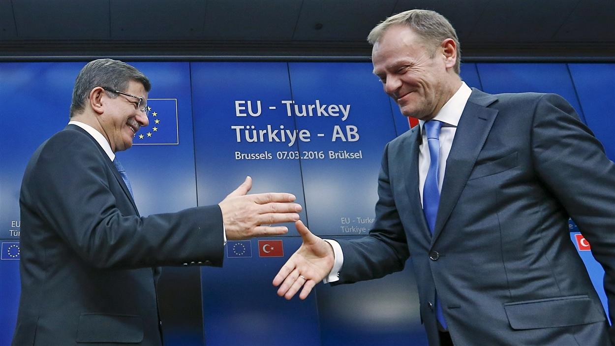 Le premier ministre turc Ahmet Davutoglu sert la main du président du Conseil européen Donald Tusk à l'issue du sommet à Bruxelles, le 8 mars 2016.