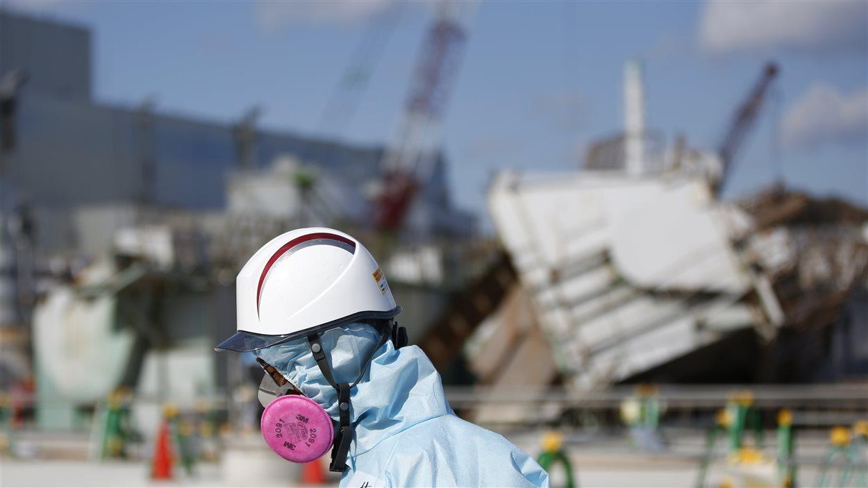 Un employé de TEPCO devant les décombres d'un des réacteurs nucléaires à Fukushima
