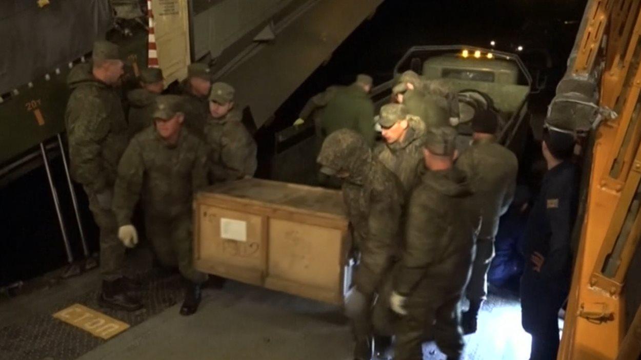 Cette photo fournie par le ministère russe de la Défense montrerait des soldats transportant du matériel militaire à bord d'un avion cargo sur la base militaire russe de Hmeymim, en Syrie.