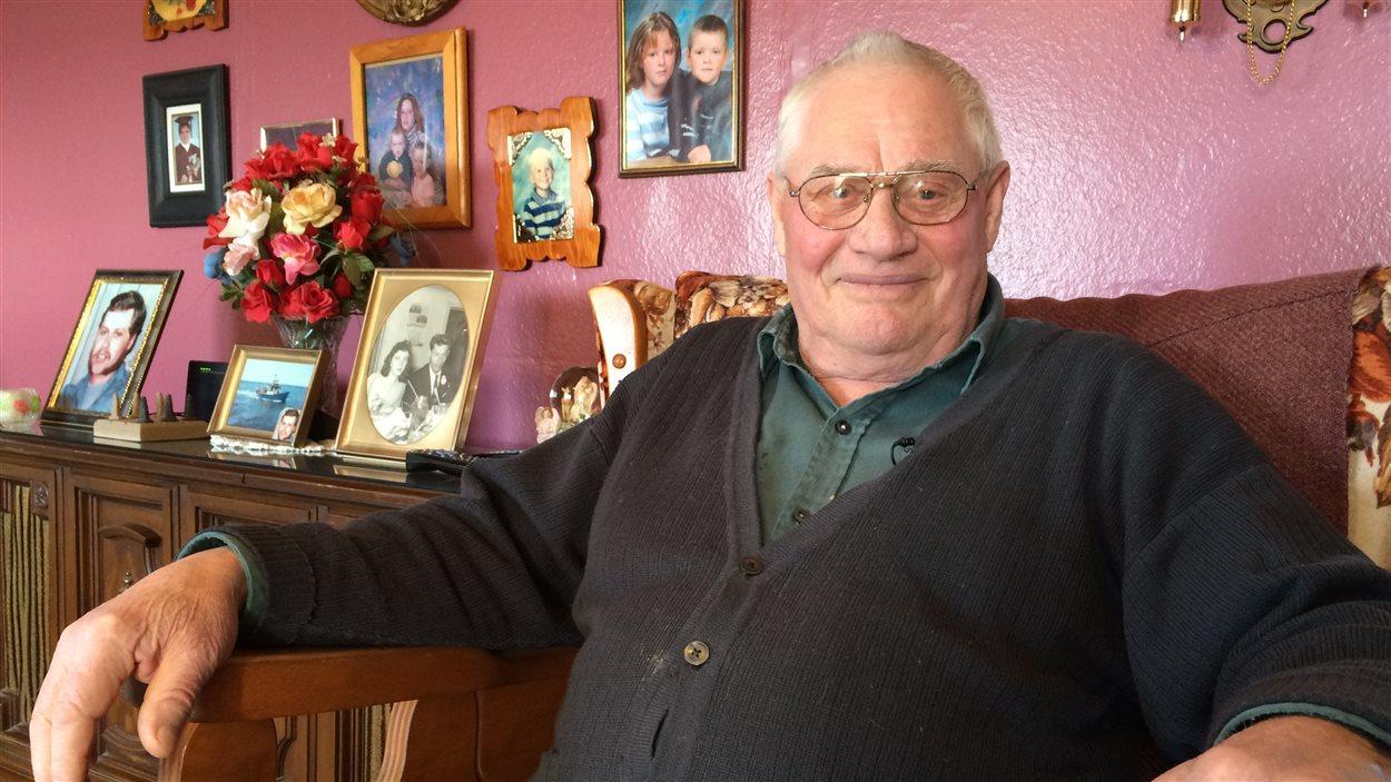 Spencer Chenell assis dans son salon devant des photos de famille.