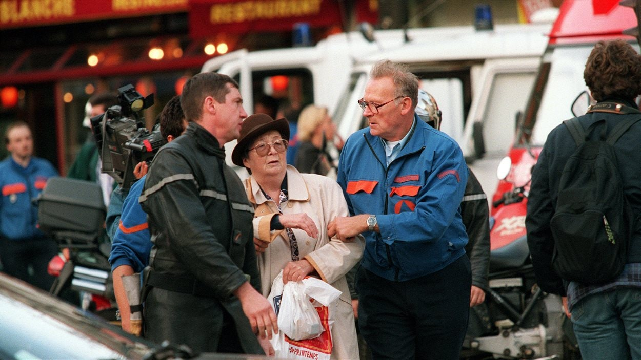 Des pompiers français aident une femme légèrement blessée à la suite de l'explosion d'une bombe le 6 octobre 1995 dans le sud de Paris près de la station de métro Maison Blanche.