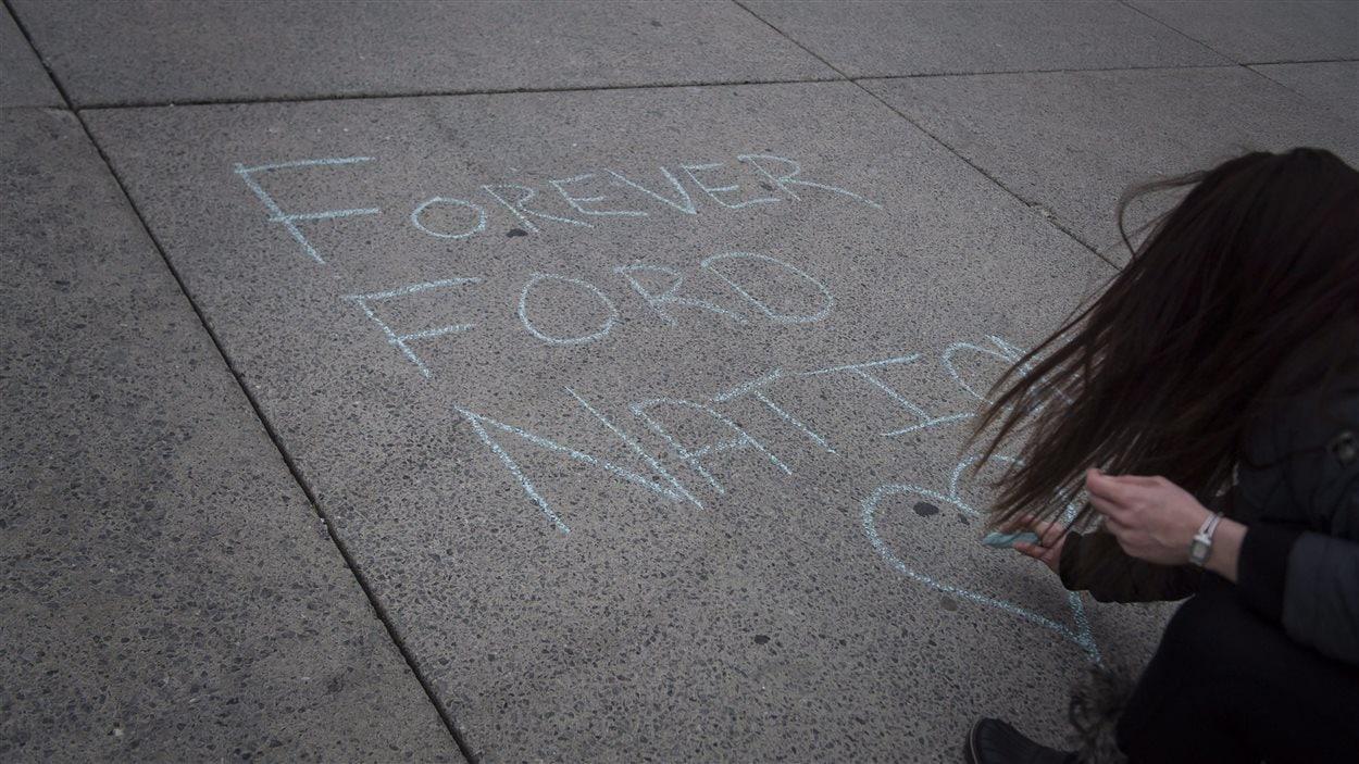 Une résidente laisse un message de condoléances à la craie pour Rob Ford sur la place de l'hôtel de ville.