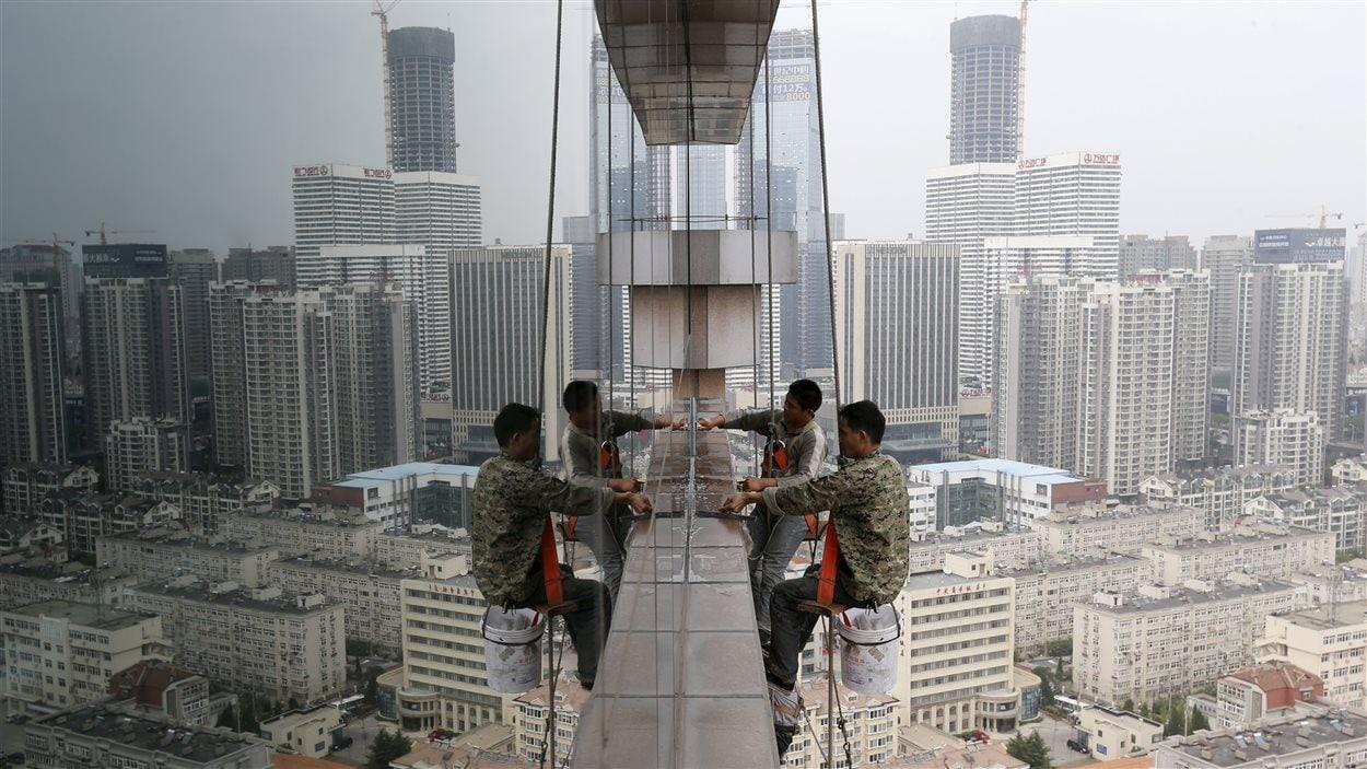 Des travailleurs nettoient les fenêtres en verre d'un bâtiment de 30 étages à Qingdao, en Chine.