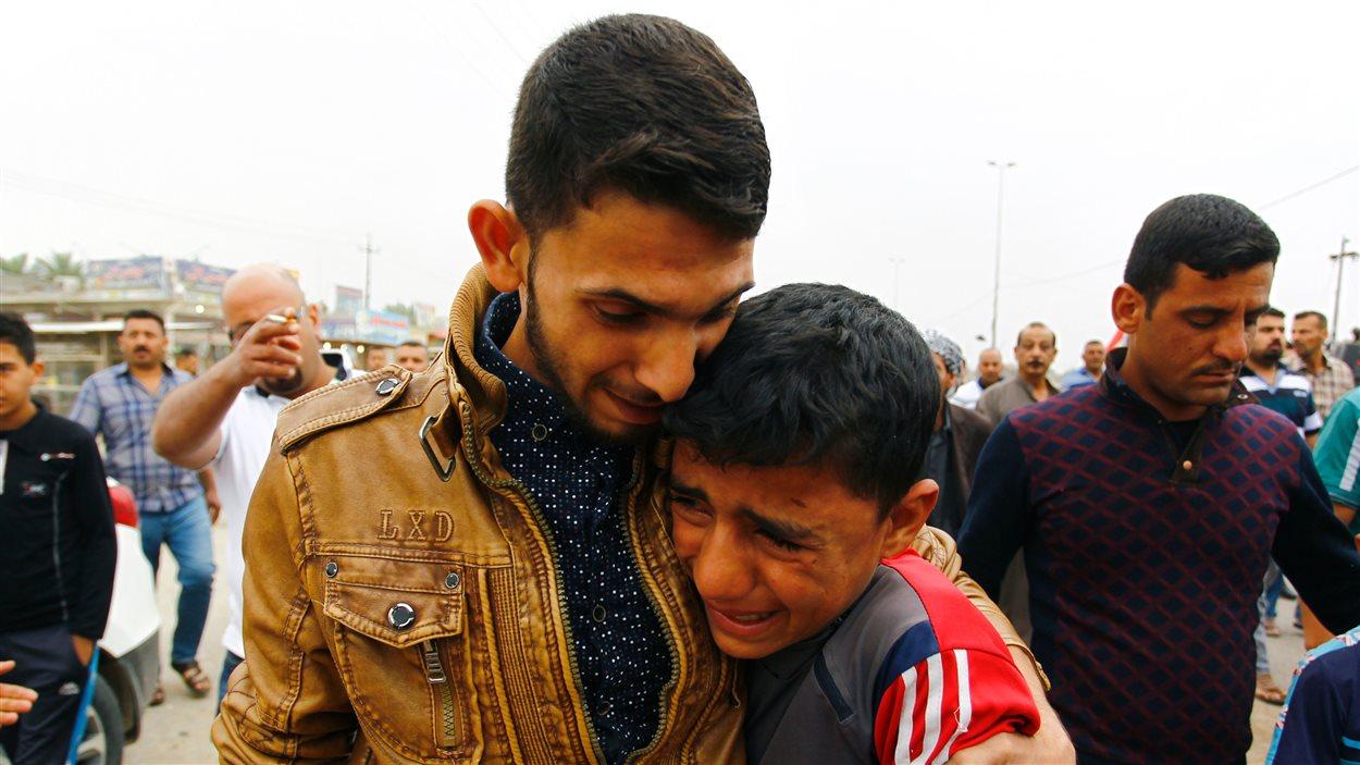 Des proches des victimes pleurent la mort de leurs amis ou de membres de leur famille après l'attentat-suicide survenu vendredi dans un stade de soccer.