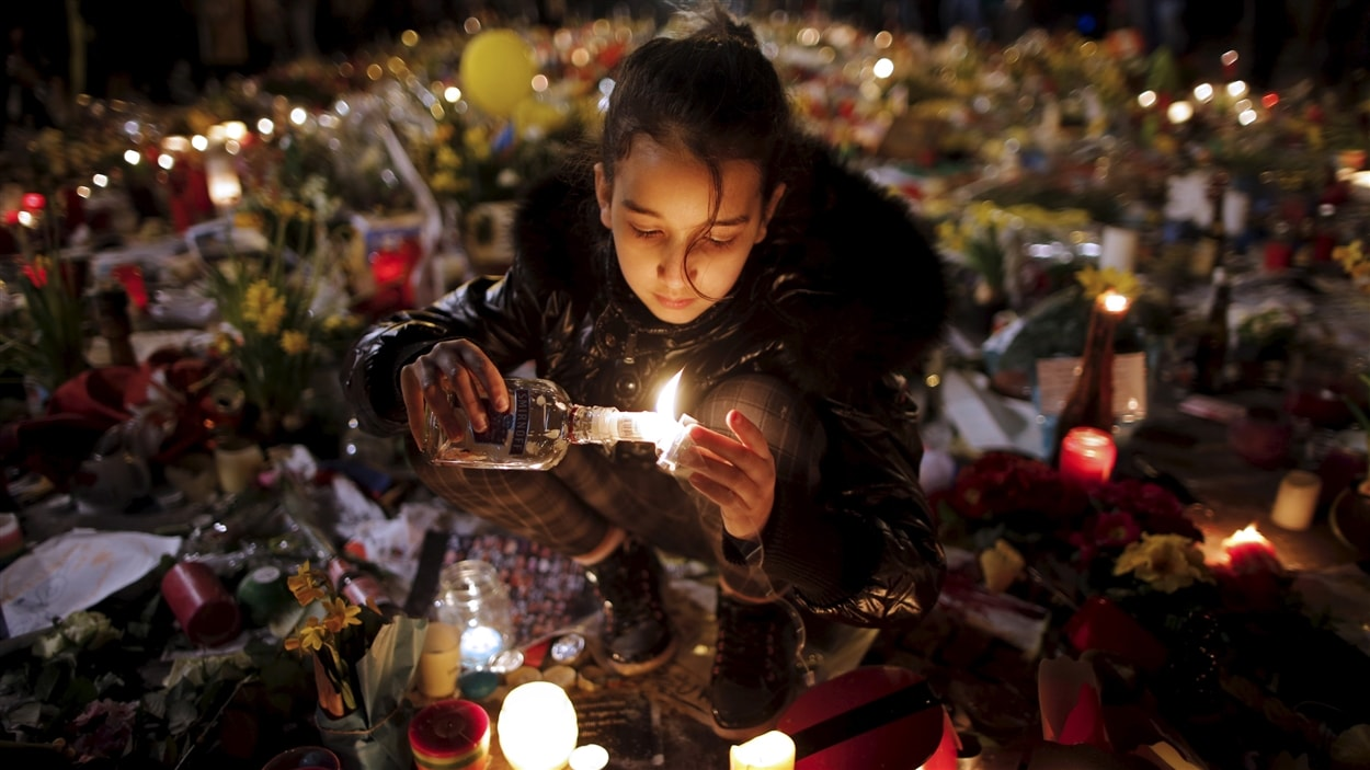 Une jeune fille allume un lampion à la Place de la bourse de Bruxelles en hommage aux victimes.