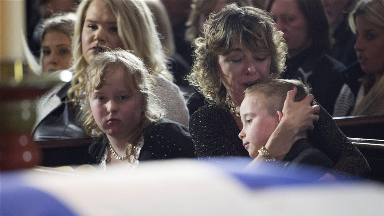 La veuve de Rob Ford serre son fils, Dougie, dans ses bras, en compagnie de sa fille, Stephanie, lors de ses funérailles.
