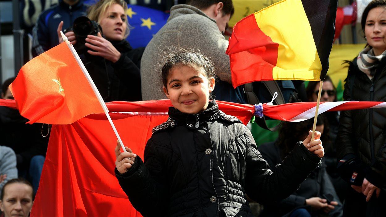 Une fillette tient des drapeaux belge et marocain lors d'un rassemblement en mémoire des victimes des attentats du 22 mars 2016,  à Bruxelles, le 27 mars 2016.